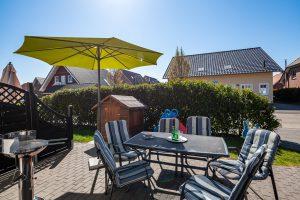 Sonnenterrasse mit Gartenmöbeln, Sonnenschirm und Kinderspielgeräten Familienurlaub