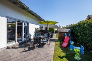 Ferienhaus Müller Fehmarn Sonnenterrasse mit Gartenmöbeln und Spielgeräten für die Kinder
