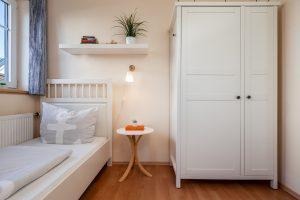 Schlafzimmer mit zwei Einzelbetten und Kleiderschrank im Ferienhaus Müller Fehmarn