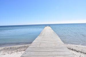Steg ins Meer am Südstrand vor blauem Himmel