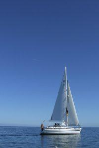 Segelboot auf offener See vor tiefblauem Himmel